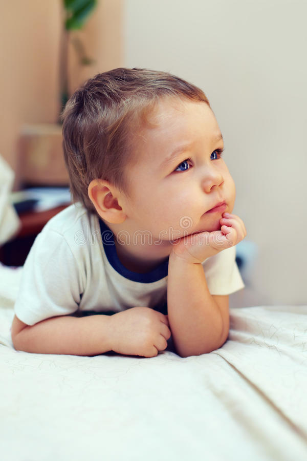Petit garçon sérieux gardant ses mains sur le menton images stock