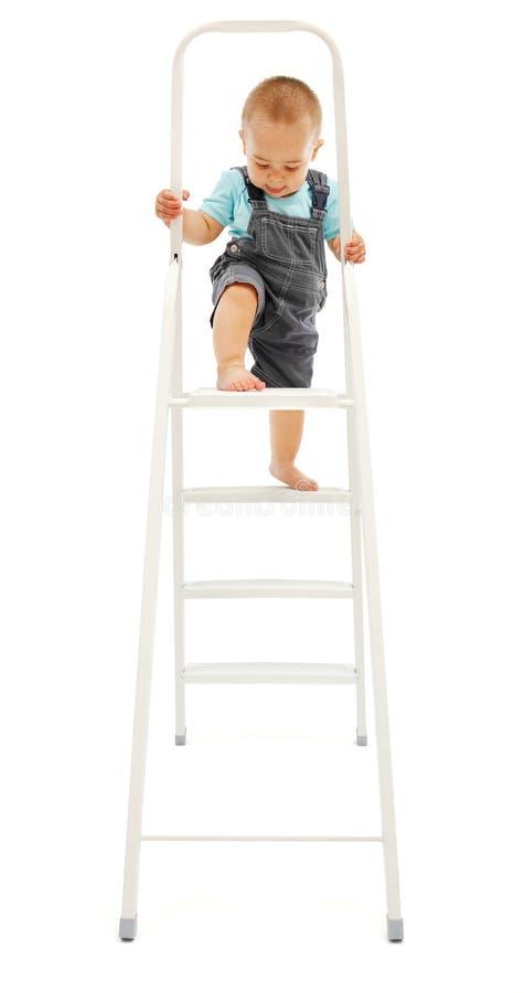 Petit garçon s'élevant vers le haut sur l'échelle photographie stock libre de droits