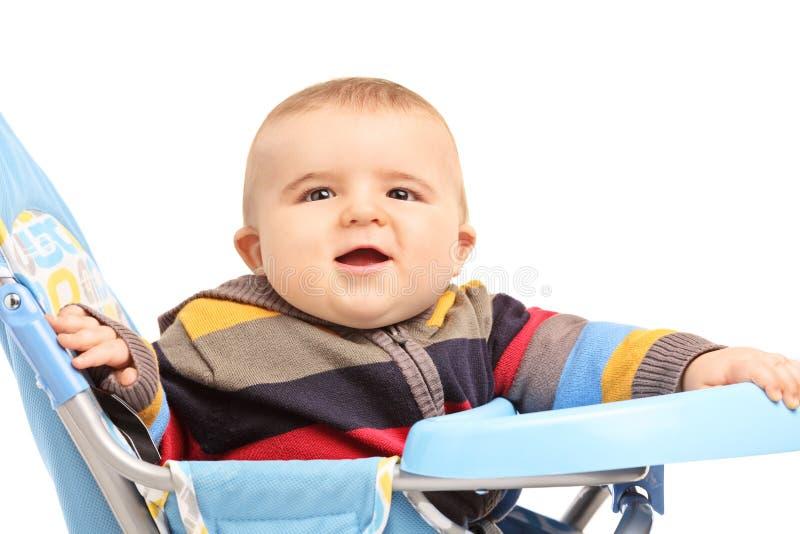 Petit garçon s'asseyant dans une poussette de bébé image stock