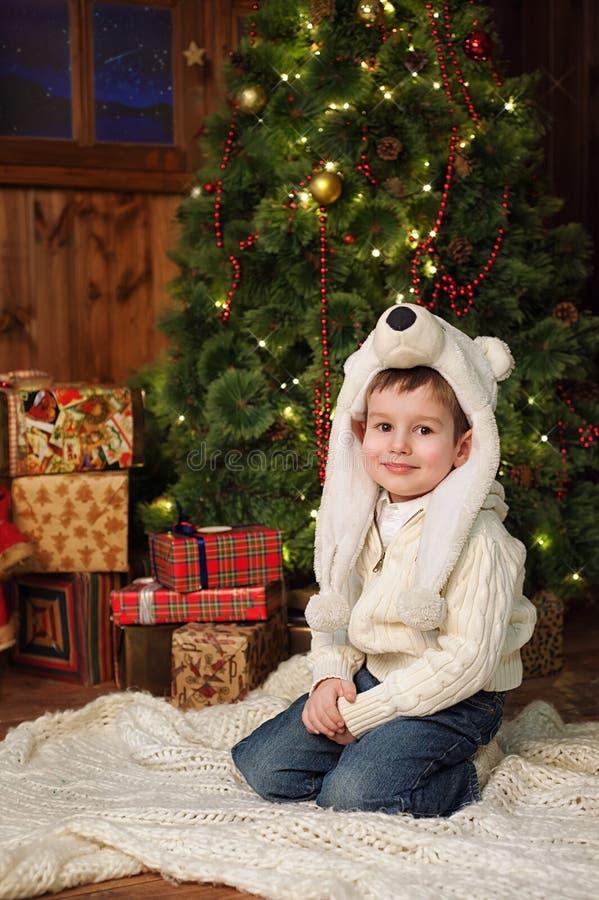 Petit garçon s'asseyant près d'un arbre de Noël photo stock