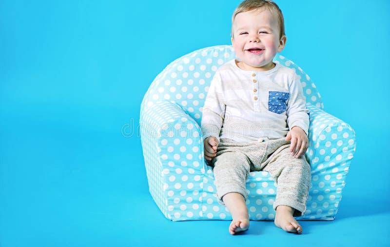 Petit garçon s'asseyant sur le fauteuil de jouet photographie stock libre de droits