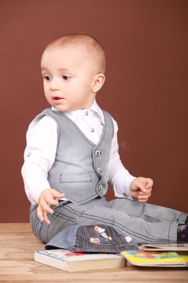 Petit garçon s'asseyant sur le plancher avec des livres photos libres de droits