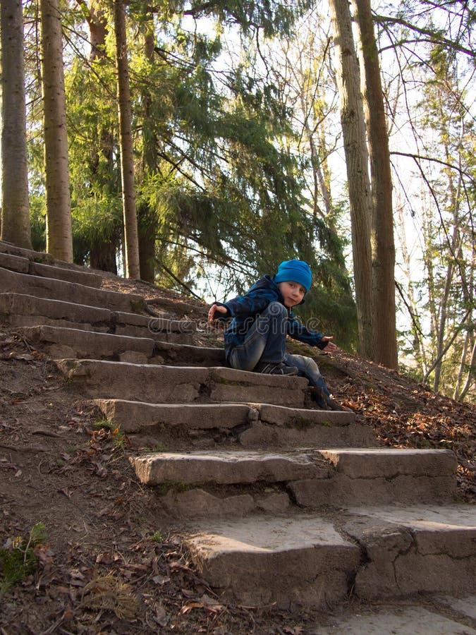 Petit garçon s'asseyant sur les escaliers photographie stock libre de droits