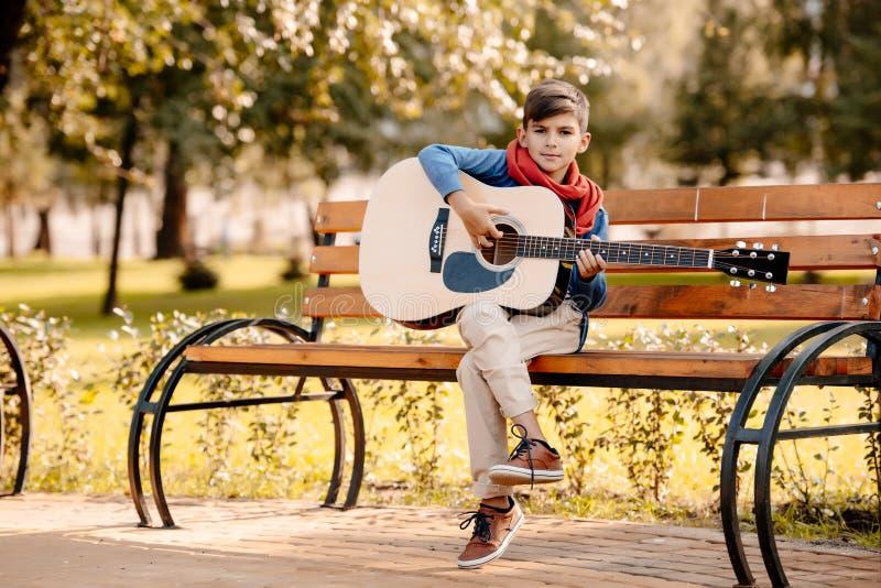 Petit garçon s'asseyant sur un banc de parc avec a photos libres de droits