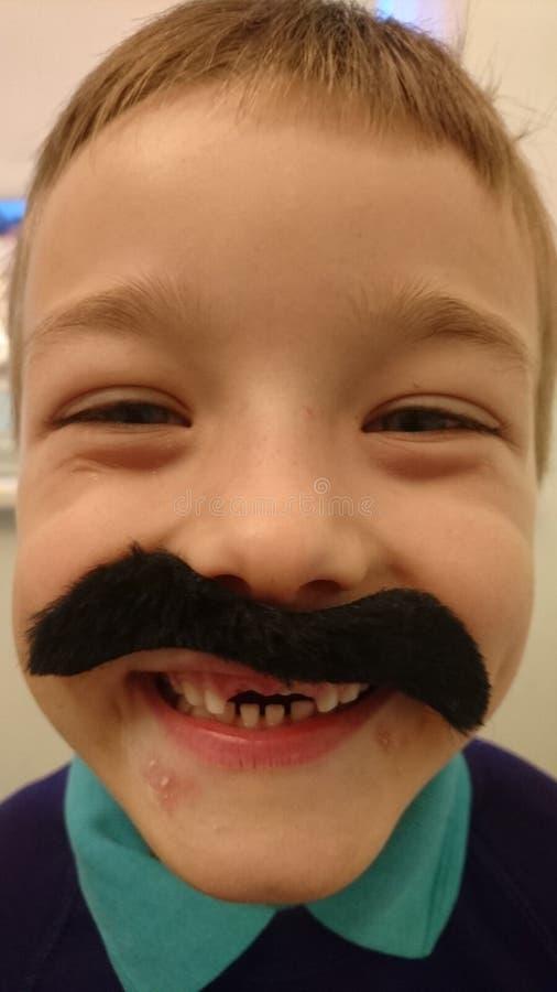 Petit garçon sans les dents avant utilisant une fausse moustache photographie stock