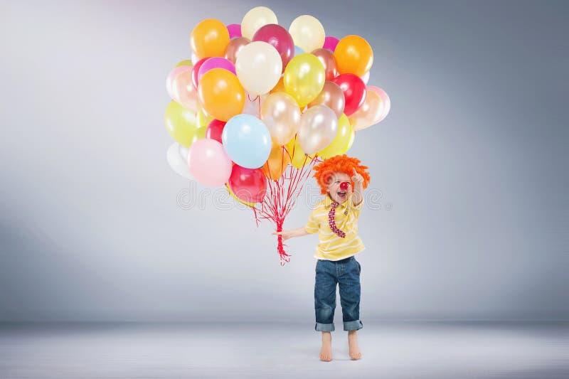 Petit garçon sautant tenant le groupe de ballons photo libre de droits