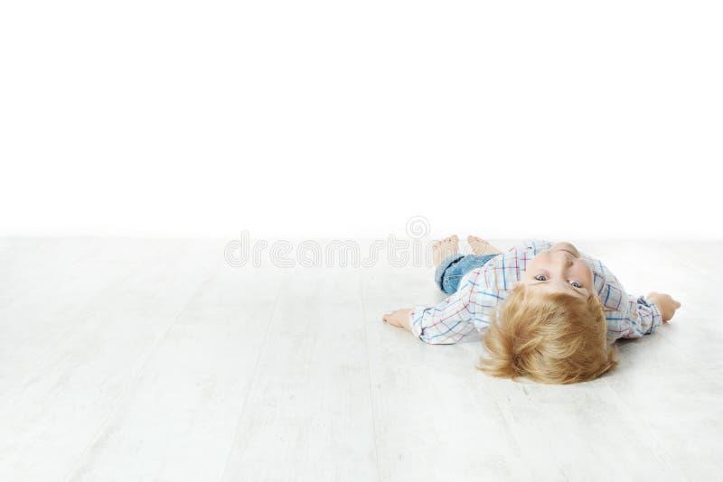 Petit garçon se couchant sur l'étage, regardant l'appareil-photo photographie stock libre de droits