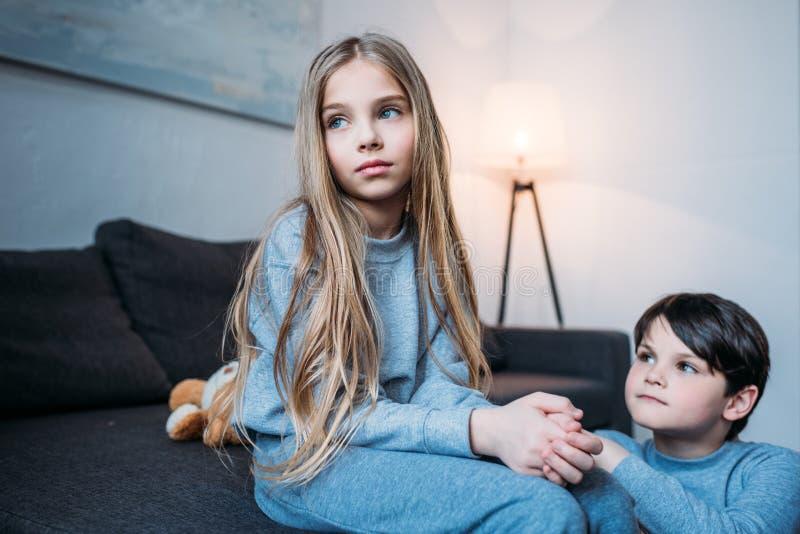 Petit garçon se mettant à genoux et regardant la petite soeur songeuse s'asseyant sur le lit photo libre de droits