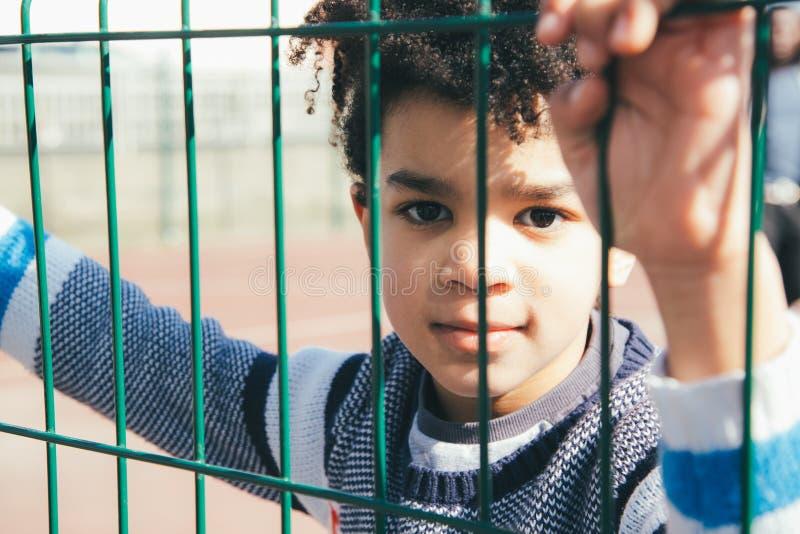 Petit garçon se penchant à la barrière en métal du terrain de jeu photos stock