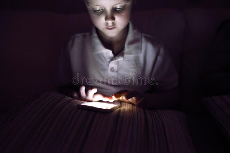 Petit garçon, se reposant dans un foncé, jouant avec le smartphone photographie stock
