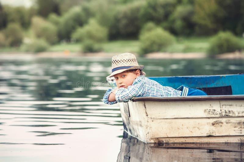 Petit garçon se situant dans le vieux bateau sur un étang à la soirée d'été images libres de droits