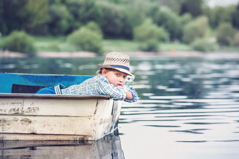Petit garçon se situant dans le vieux bateau sur un étang à la soirée d'été image stock