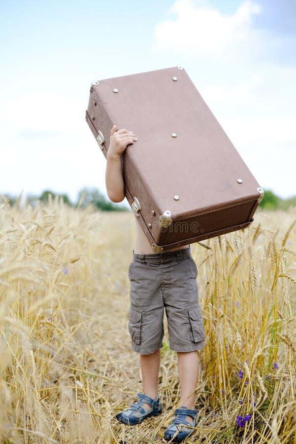 Petit garçon se soulevant vers le haut de la grande vieille valise dans le blé photo stock