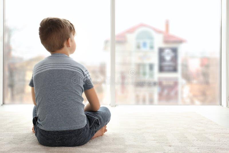Petit garçon seul s'asseyant sur le plancher dans la chambre photos libres de droits