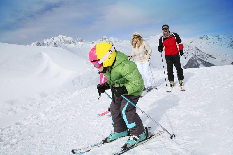 Petit garçon skiant les pentes avec ses parents images libres de droits