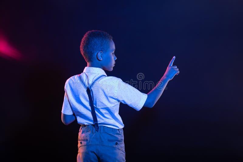 Petit garçon sombre appuyant sur un bouton imaginaire photo libre de droits