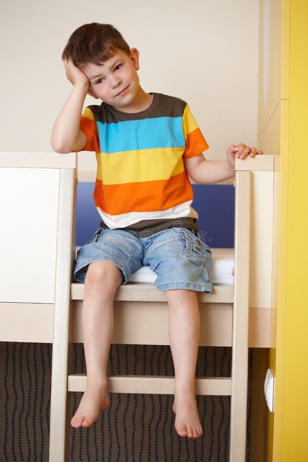 Petit garçon somnolent sur le bâti de couchette photographie stock libre de droits