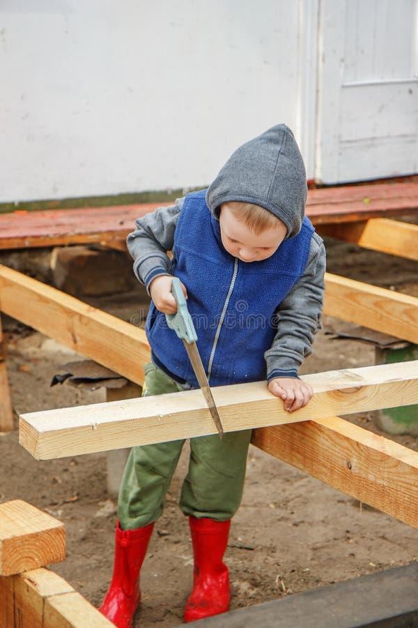 Petit garçon studieux sciant un conseil en bois Construction à la maison Li photographie stock