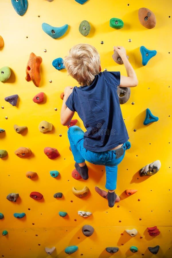 Petit garçon sur le mur s'élevant image libre de droits