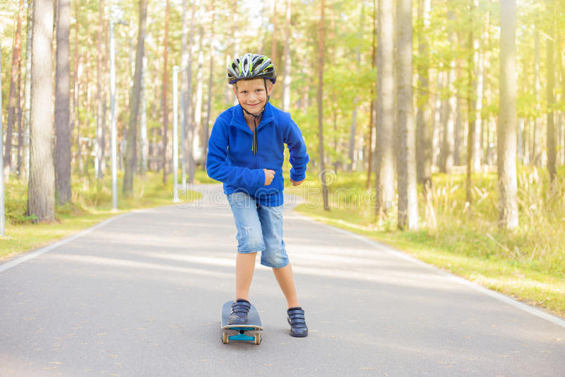 Petit garçon sur le panneau de patin photos stock