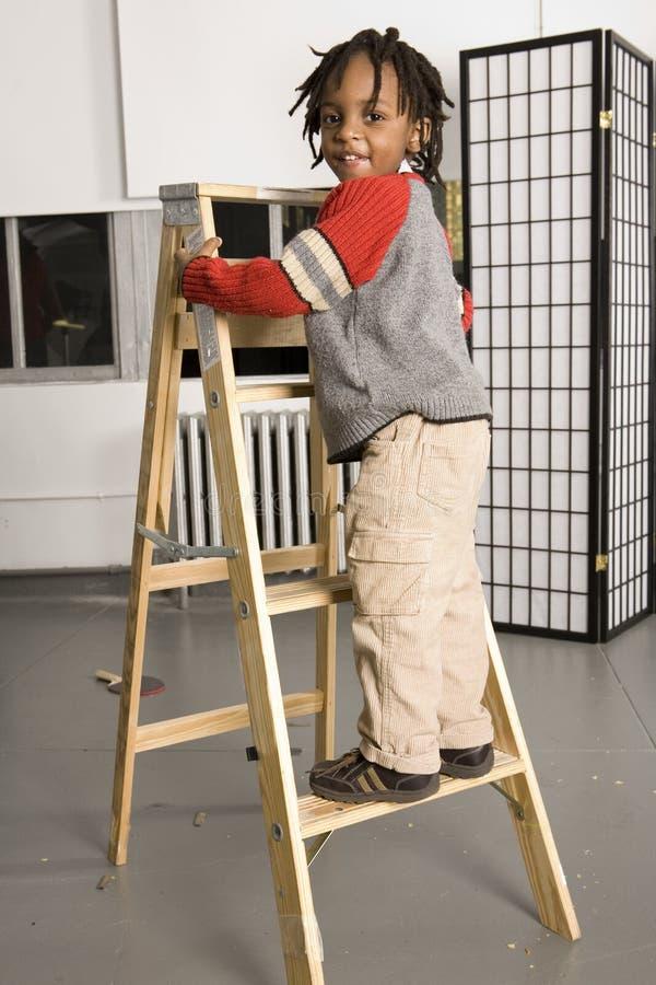 Petit garçon sur une échelle photographie stock
