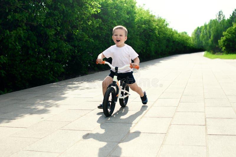 Petit garçon sur une bicyclette Attrapé dans le mouvement, sur une allée Presch photo libre de droits