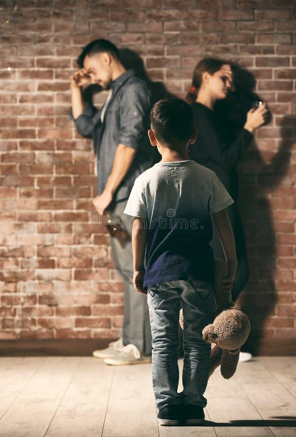 Petit garçon tenant l'ours de nounours tandis que ses parents ayant la querelle photos libres de droits