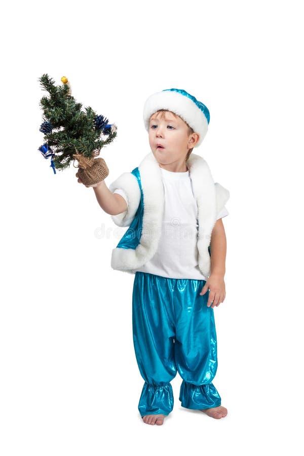Petit garçon tenant un arbre de Noël dans sa main image stock