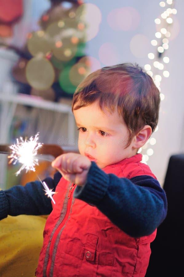 Petit garçon tenant un bâton d'étincelle photos stock