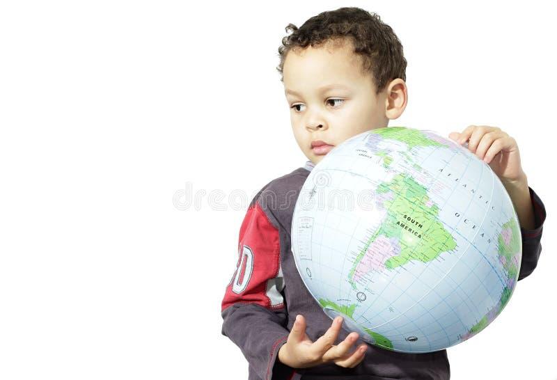 Petit garçon tenant un globe images stock