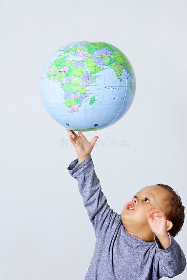 Petit garçon tenant un globe photo stock