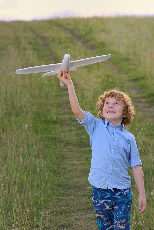Petit garçon tenant un modèle en bois d'avion image libre de droits