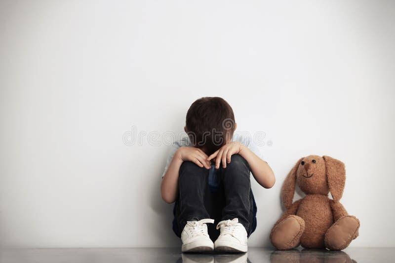 Petit garçon triste avec le jouet se reposant près du mur blanc image libre de droits