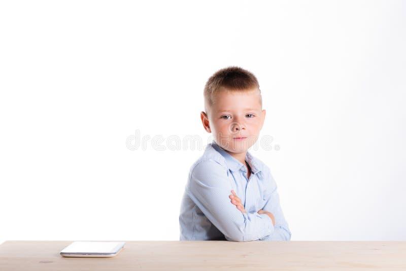 Petit garçon triste dans le costume se reposant à la table avec l'instrument de comprimé Chil image libre de droits