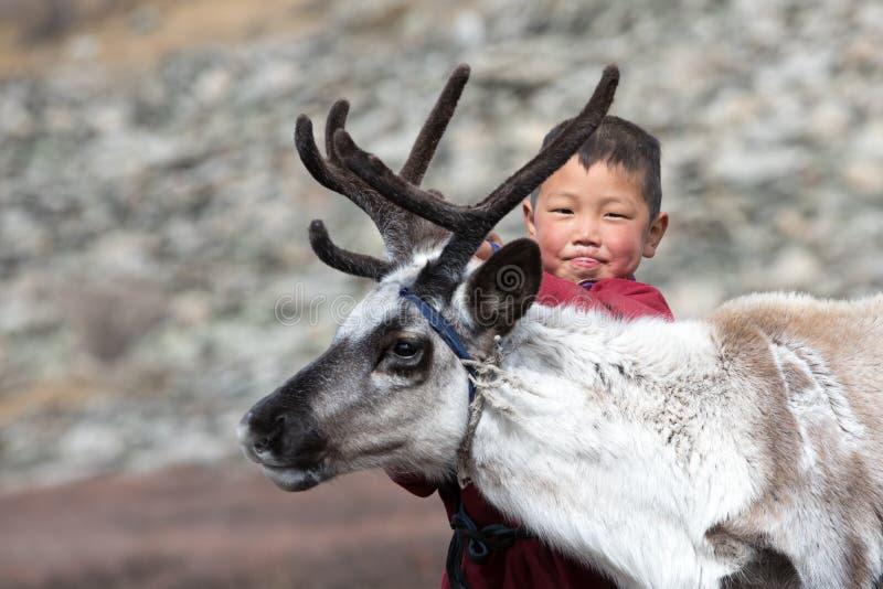 Petit garçon tsaatan jouant avec son renne du ` s de famille photographie stock libre de droits