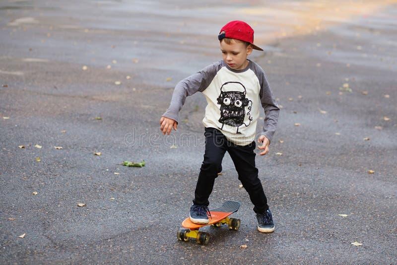 Petit garçon urbain avec une planche à roulettes de penny Équitation de jeune garçon en Th photo stock