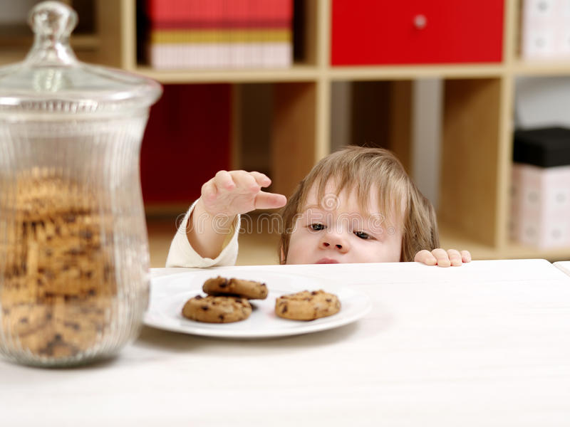 Petit garçon volant des biscuits image stock