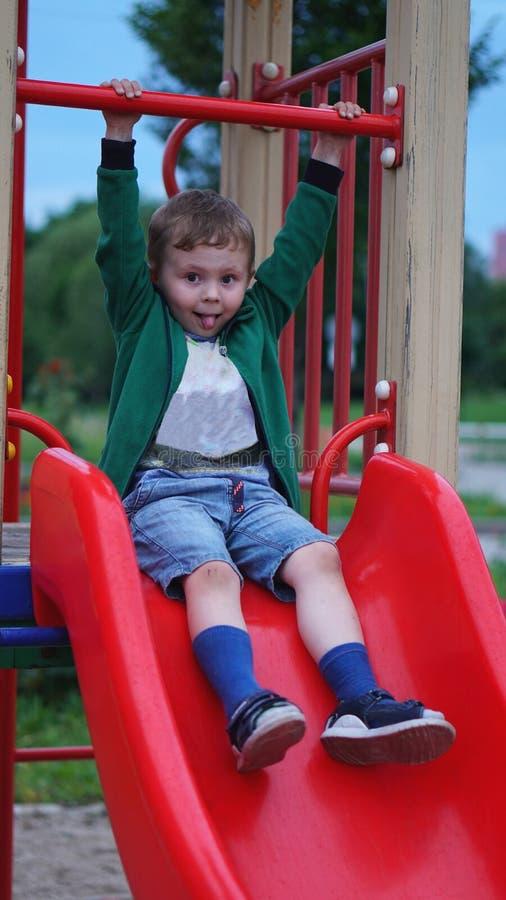 Petit gar?on ayant l'amusement sur un terrain de jeu dehors en ?t? Enfant en bas ?ge sur une glissi?re photo stock