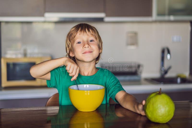 Petit gar?on blond heureux d'enfant mangeant des c?r?ales pour le petit d?jeuner ou le d?jeuner Consommation saine pour des enfan photo stock