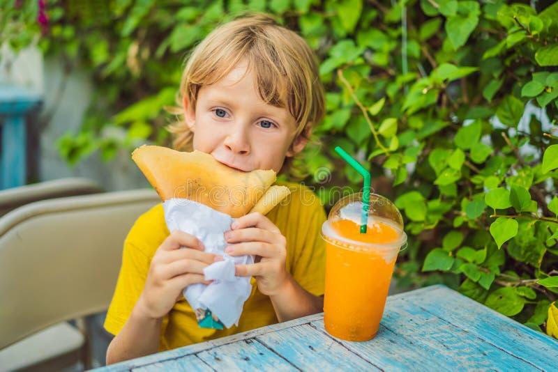 Petit gar?on caucasien doux, mangeant des cr?pes et buvant du jus d'orange photo stock