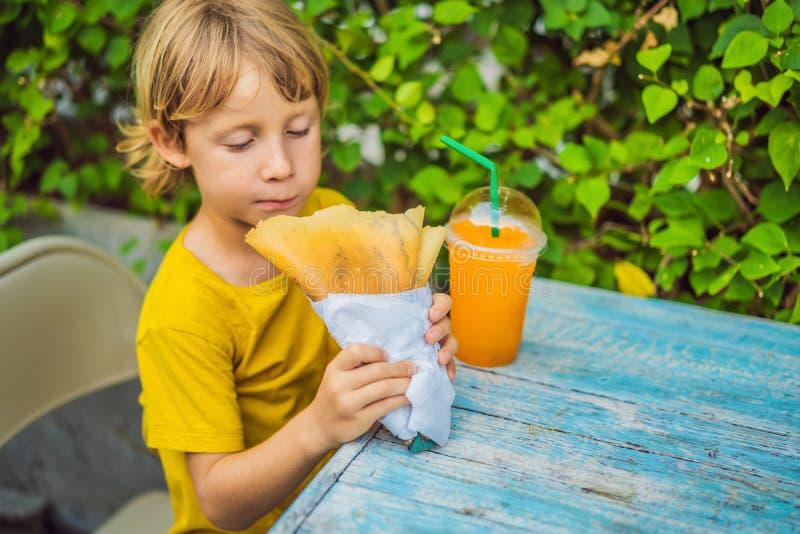 Petit gar?on caucasien doux, mangeant des cr?pes et buvant du jus d'orange image stock