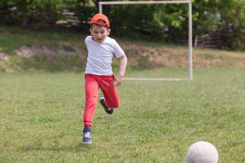 Petit gar?on donnant un coup de pied la boule en parc jouer le football du football en parc sports pour l'exercice et l'activit? image libre de droits