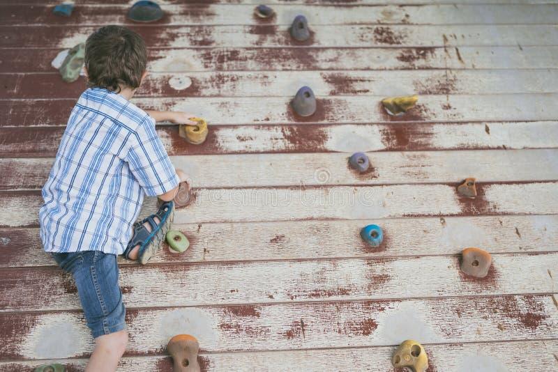 Petit gar?on escaladant un mur de roche ext?rieur images stock
