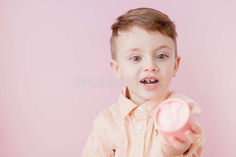 Petit gar?on heureux avec un cadeau photo sur le fond rose Le gar?on de sourire tient la bo?te actuelle Concept des vacances et d photo stock