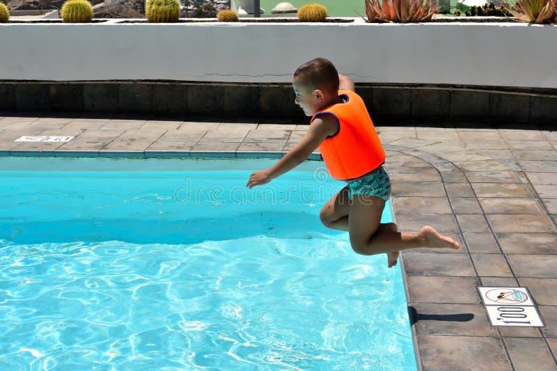 Petit gar?on sautant dans la piscine photographie stock libre de droits
