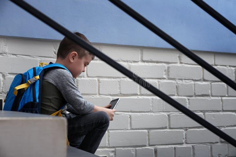 Petit gar?on triste avec le t?l?phone portable se reposant sur des escaliers photographie stock libre de droits