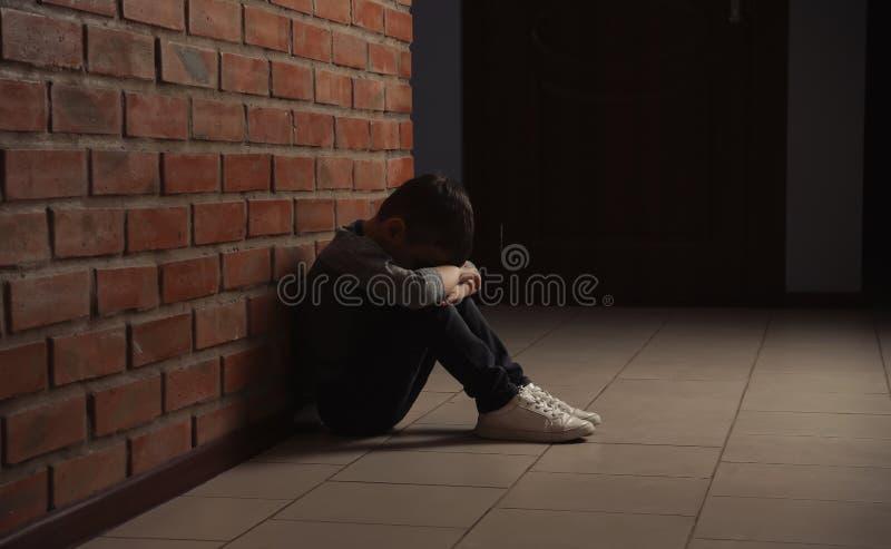 Petit gar?on triste s'asseyant sur le plancher pr?s du mur de briques photo stock