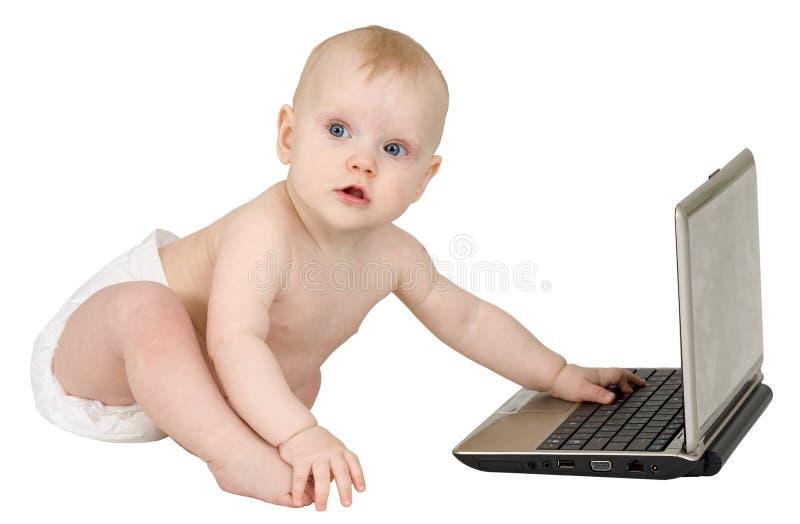 Petit gentil enfant avec l'ordinateur portatif d'isolement sur le blanc image libre de droits