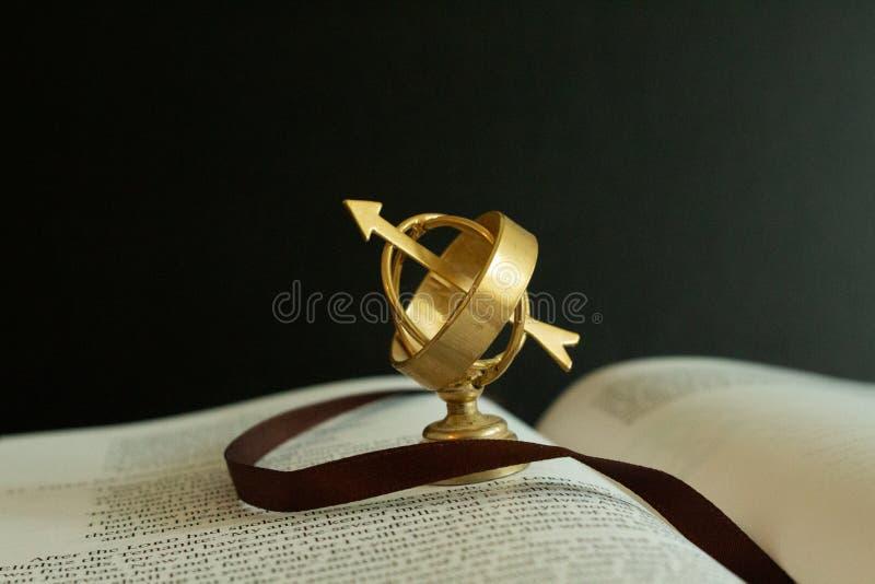 Petit globe miniature d'astrolabe sur un livre ouvert images stock
