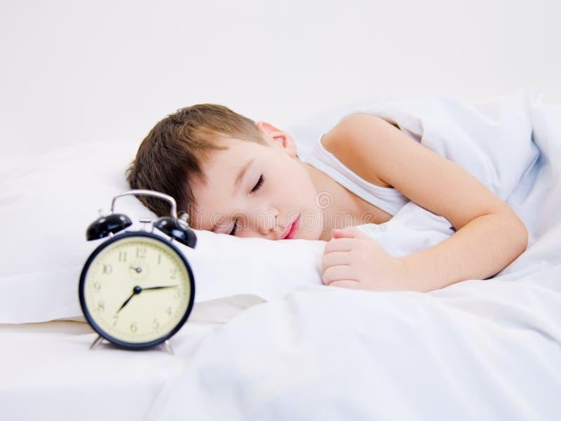 Petit gosse dormant avec l'horloge près de sa tête photographie stock libre de droits